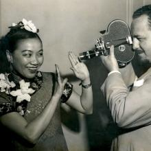 Black and white photo  of a filmmaker filming  Li Ling-Ai, who is smiling, and acting shy.