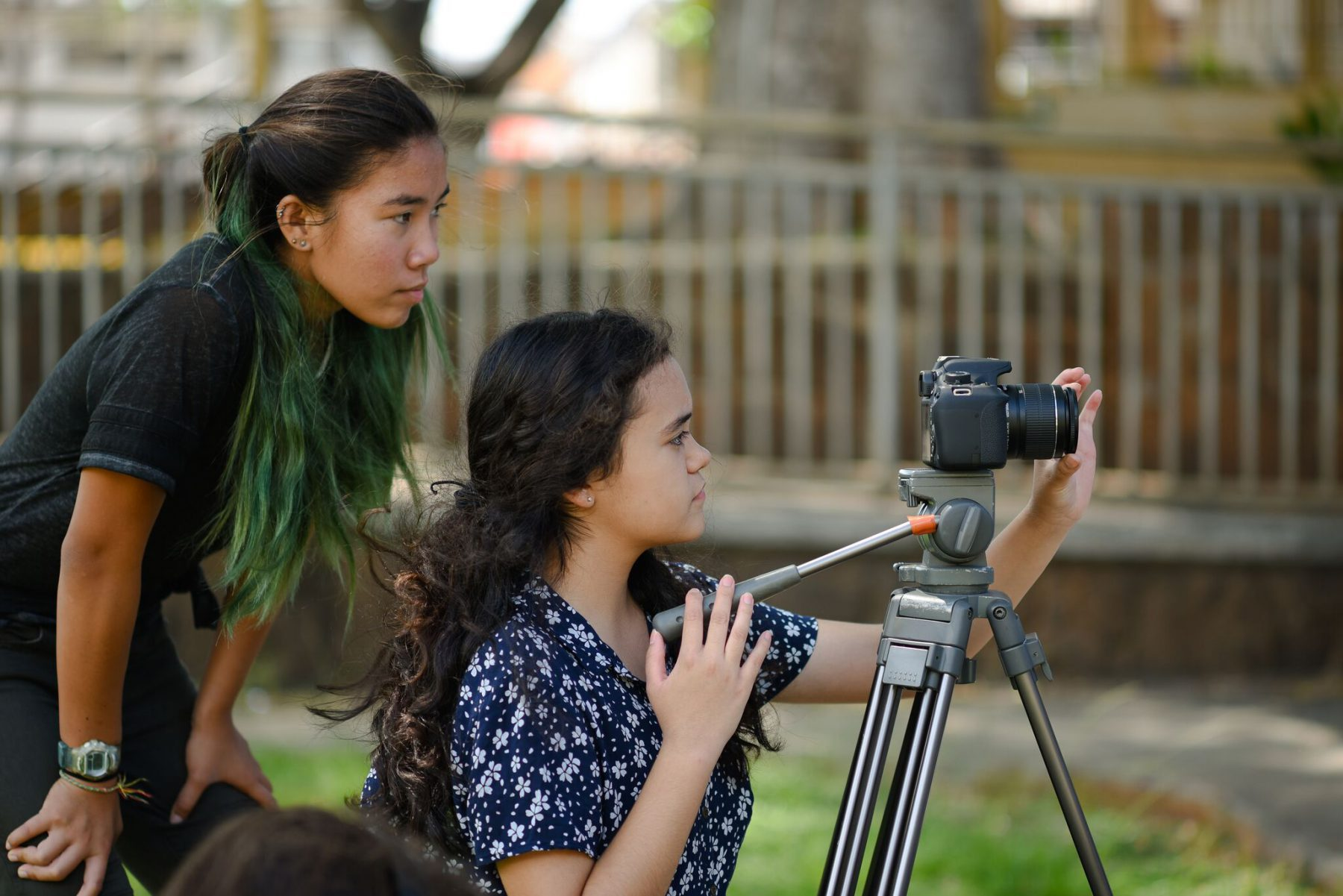 Young women adjusting and using video camera equipment.