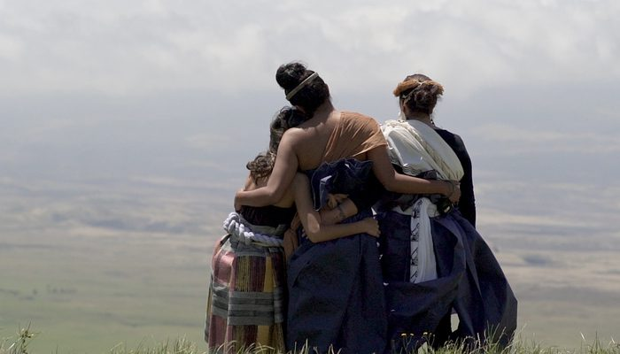 Three Women arm-in-arm looking out over the plains in Hawai'i