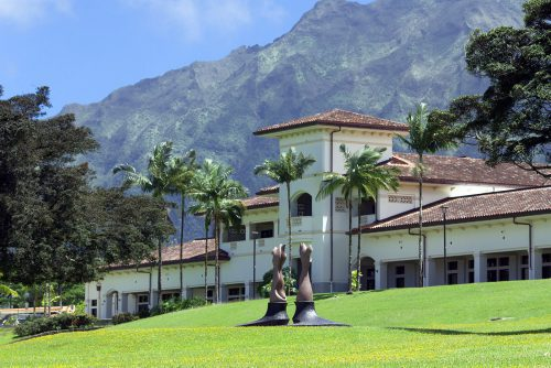 Hale 'Ākoakoa building surrounded by trees with Ko'olau Mountains behind it