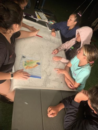 students sitting around a map and having discussion