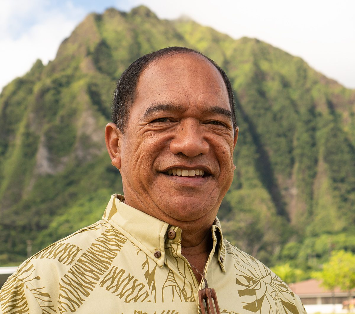 Kimo Adams standing with Koolau mountains behind him in the sun