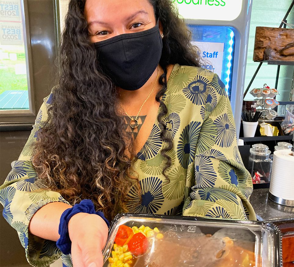 Alisha Kaluhiokalani presenting a bento from Meals With A Mission and wearing a mask